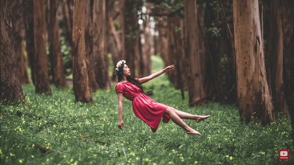 Levitating girl with pink dress in the forest