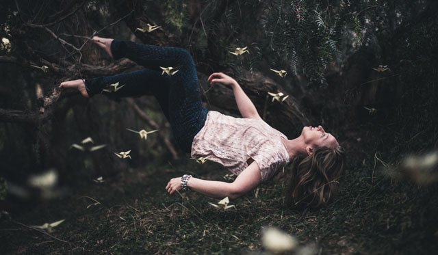 Levitating woman in a mystical forest