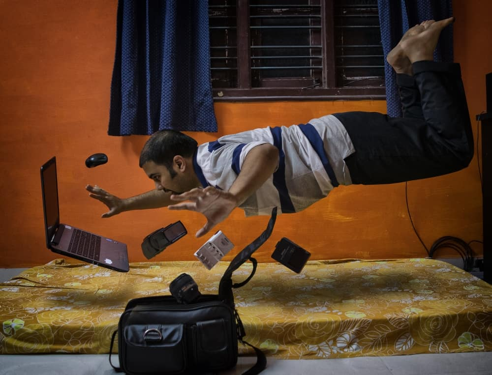 Levitating man from the bed with computer