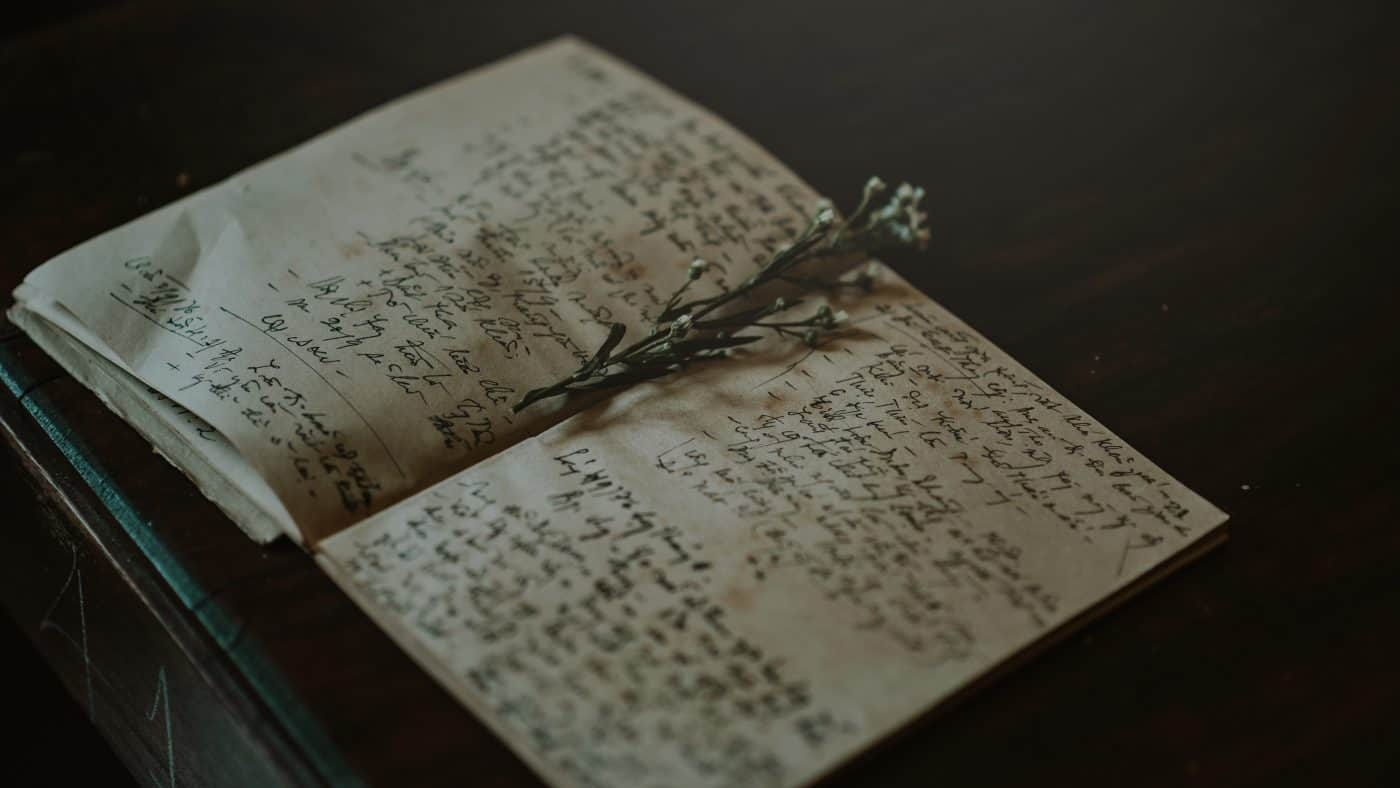 Opened book with writing and flower