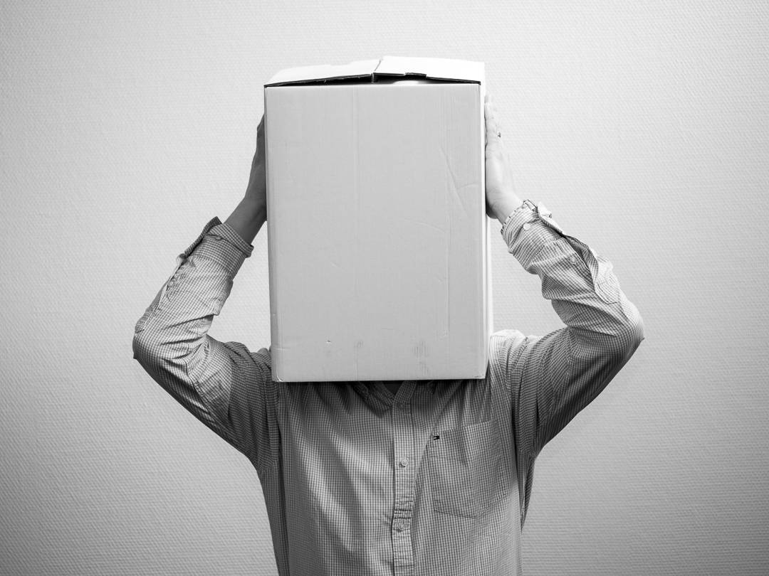 man with his head inside a box