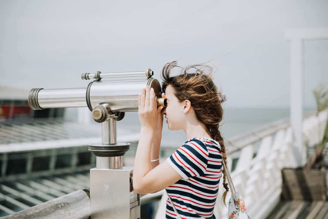 young woman looking through a spyglass
